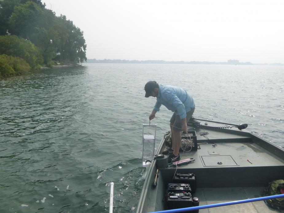 A person at the front of a boat pulls a clear box sampler out of the water.