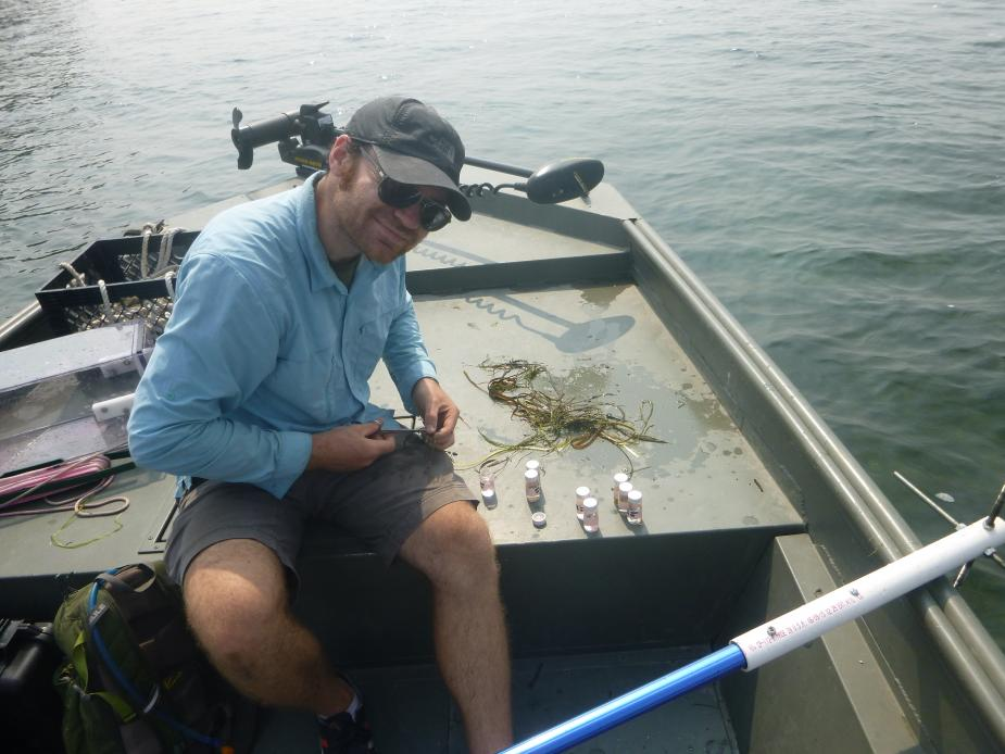 A person sitting on the front of a boat. There are vials arranged next to them and a pile of underwater grasses.