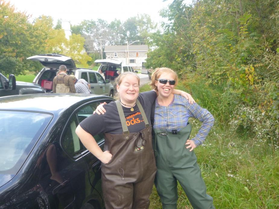 Two people wearing chest waders pose together next to a car. Trees and a few cars and people are in the background.