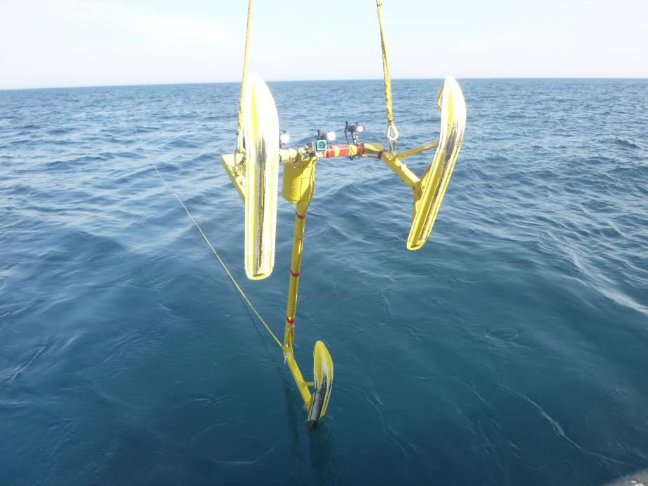 A metal frame with sled feet is lowered into the water.