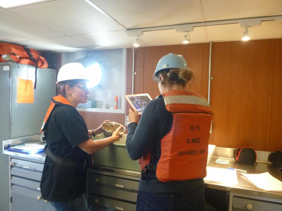 A person holds up a bowl of mud while another person points a tablet at it to record an image or video. They are both wearing hard hats and life jackets inside a lab.