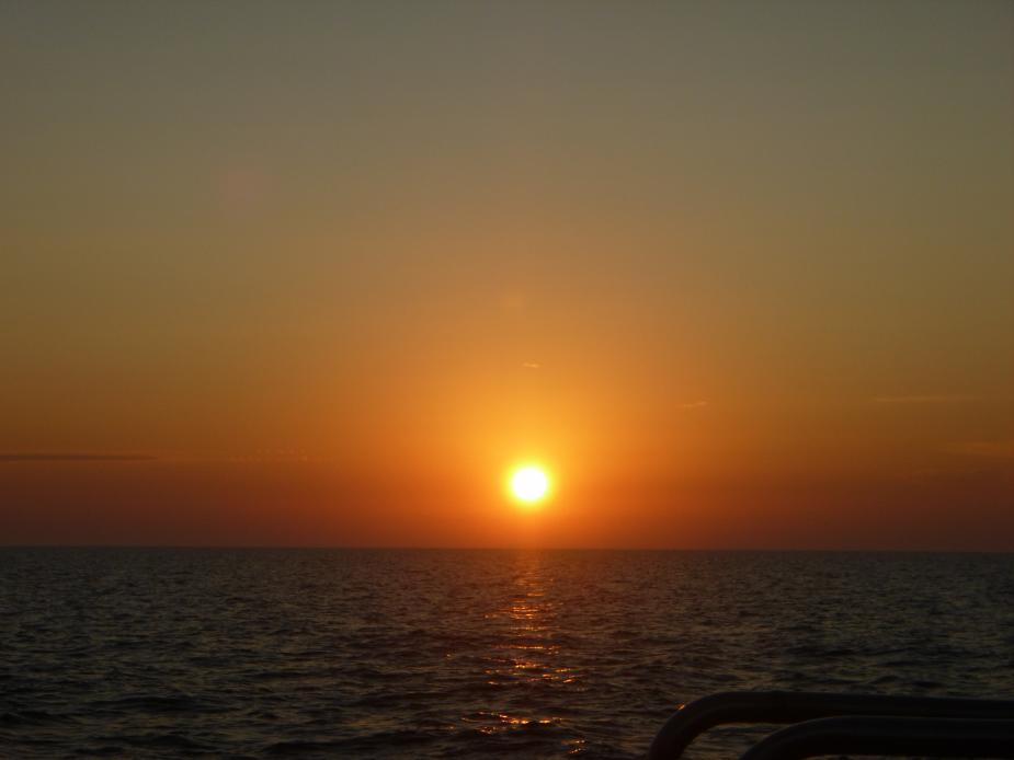 Sunrise over water. The sky is cloudless but hazy, intense red by the horizon and yellow for much of the sky above that. The sun is bright yellow.