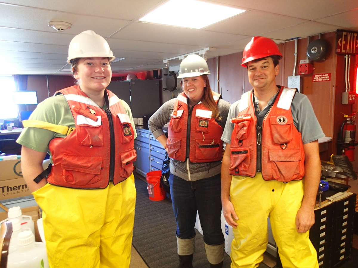 Three people inside wearing hard hats, life jackets, and rain pants.