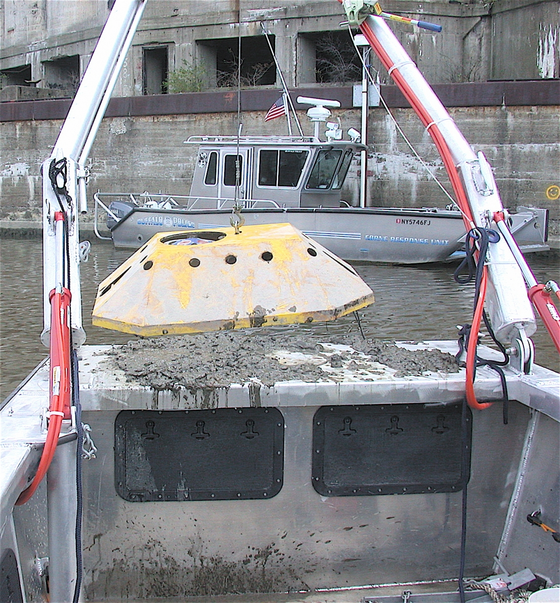The frame on the front of a boat is used to lift a large metal device. There is mud on the boat. The boat is facing another boat labeled