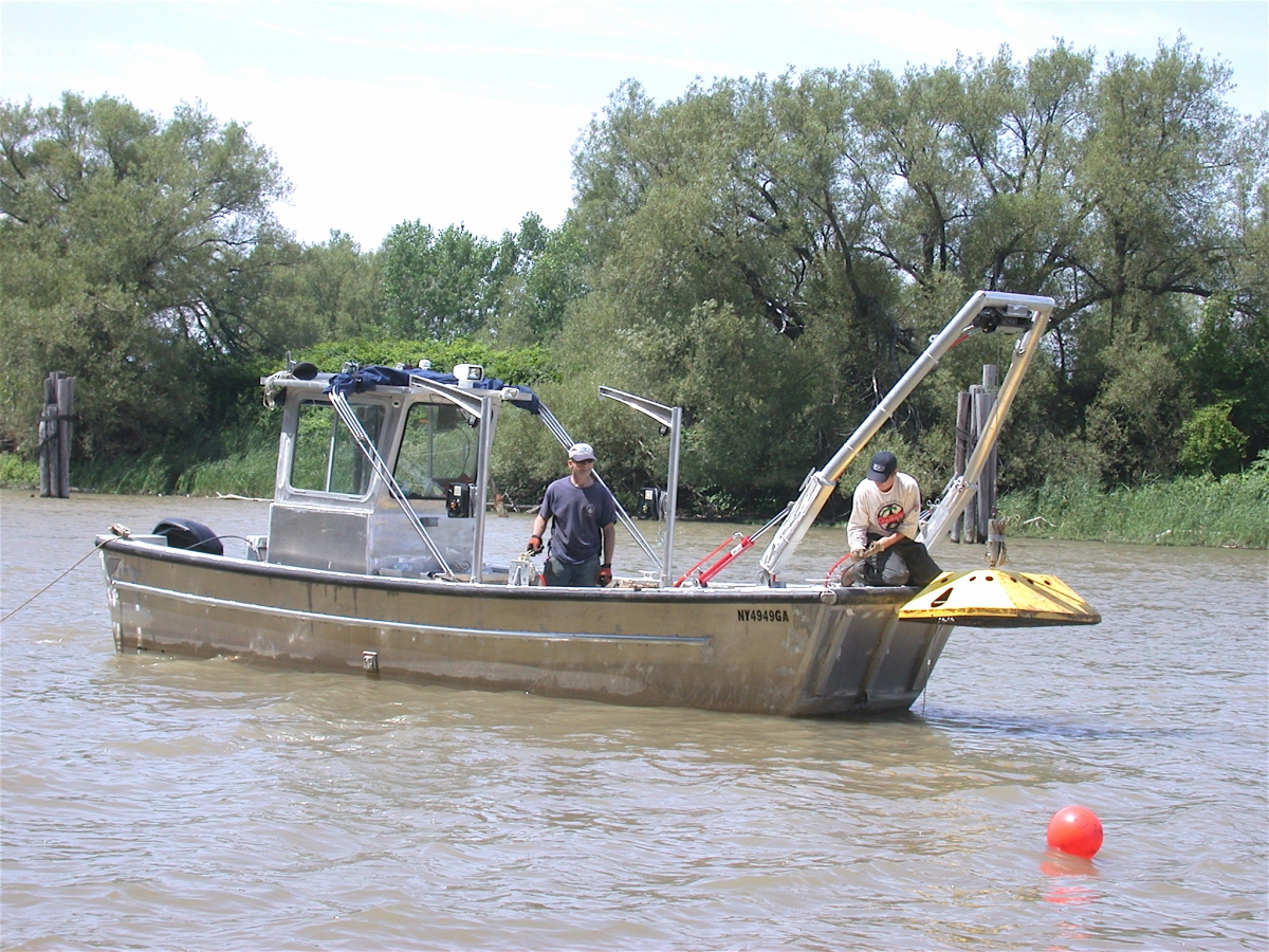 Two people on a boat. The frame on the front of the boat is lifting a large metal device.