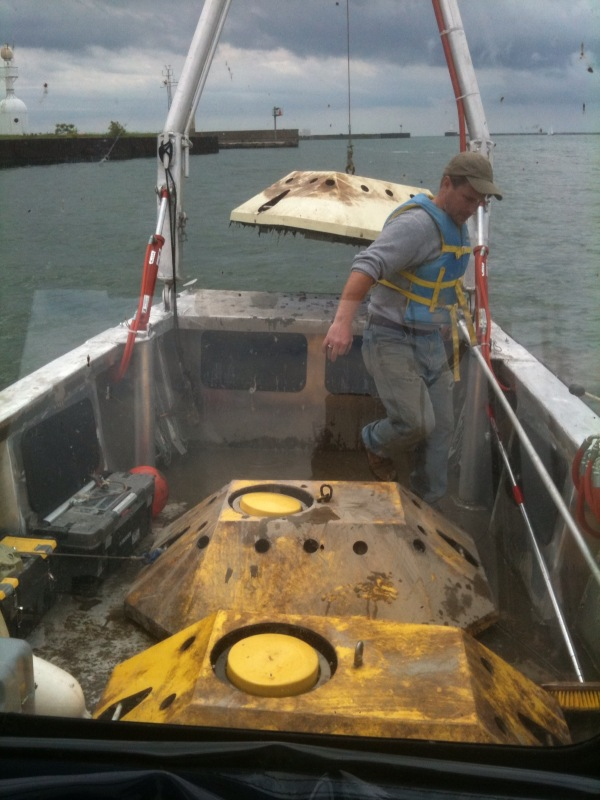 A person in the front of a boat. There are two large metal devices on the deck and the frame at the front of the boat is lifting a third one.