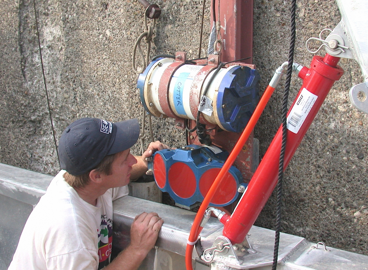 A person looks at some equipment attached to the side of a wall