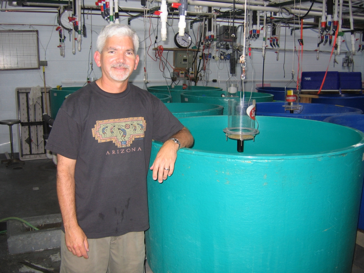 A person stands with their arm resting on a round green tank in a lab. Their shirt says