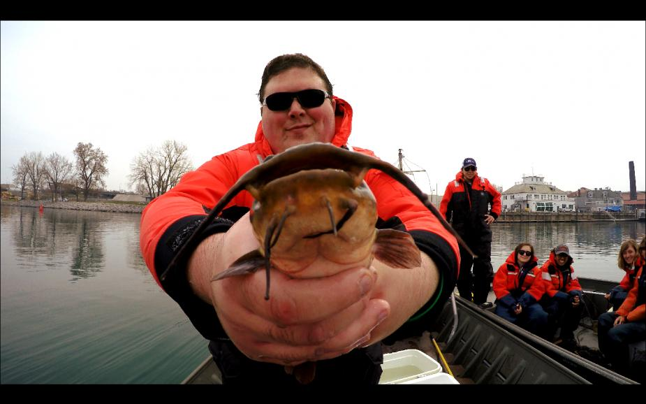 Student holds up a brown bullhead to the camera. There are students in a second boat in the background.