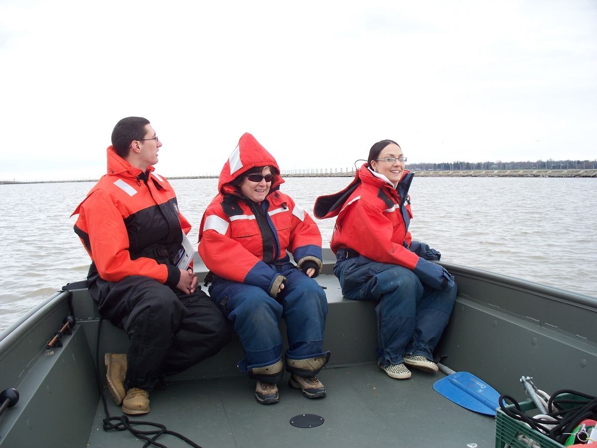 Three people sitting at the front of a boat wearing flotation suits