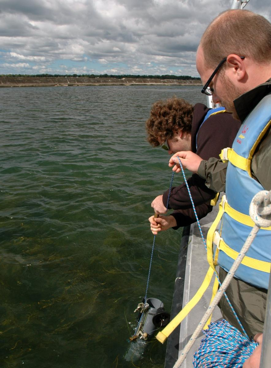 a student at the edge of the boat pulls up a plastic tube while another student watches