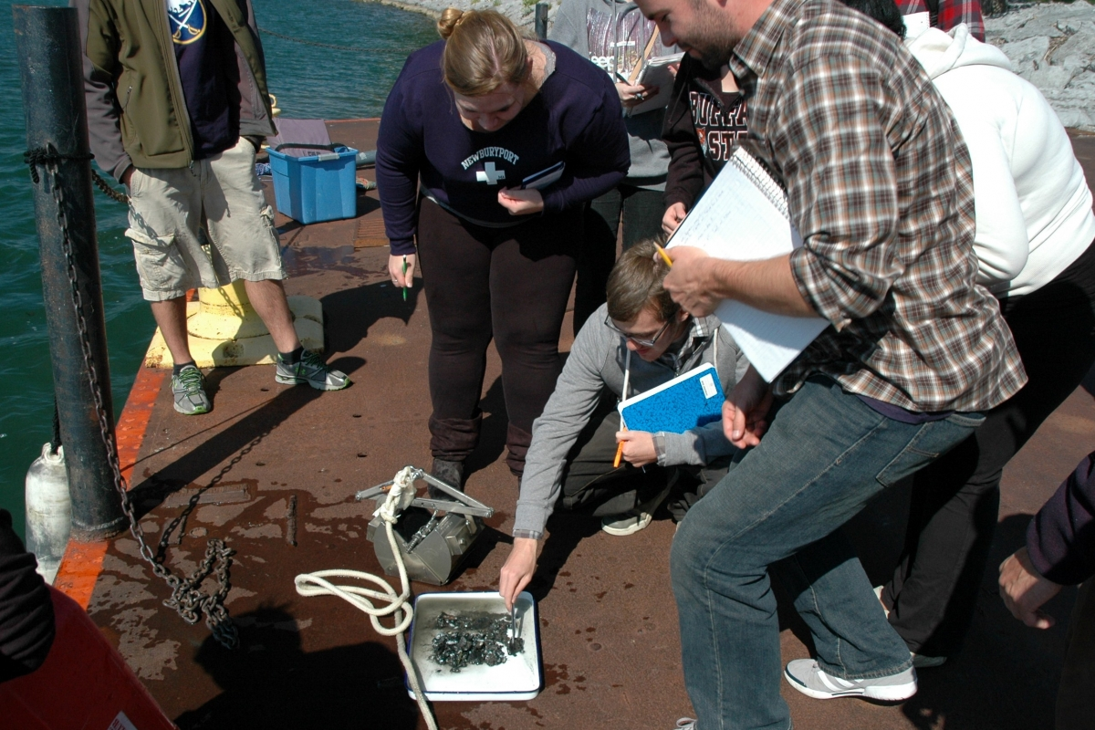 A group of students stand around as someone looks at a muddy sample in a pan. A metal contraption sits next to the pan on the dock