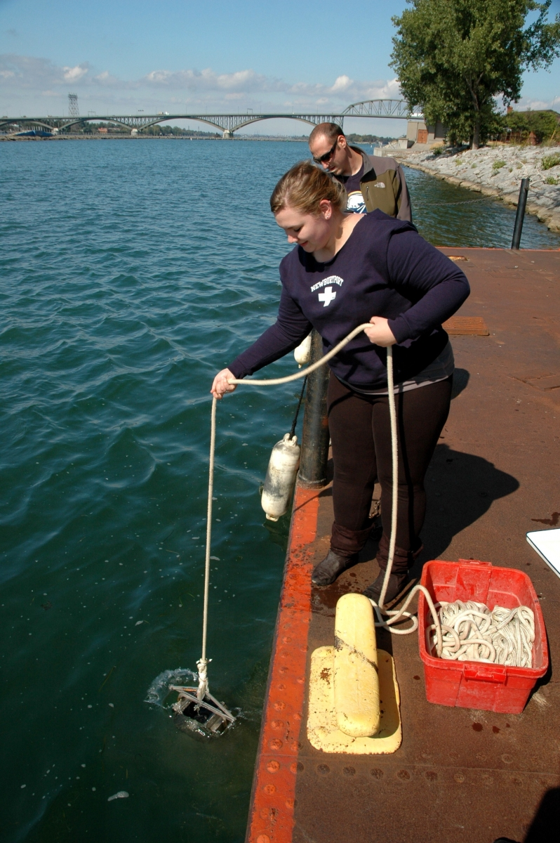 A person lowers a metal contraption into the water