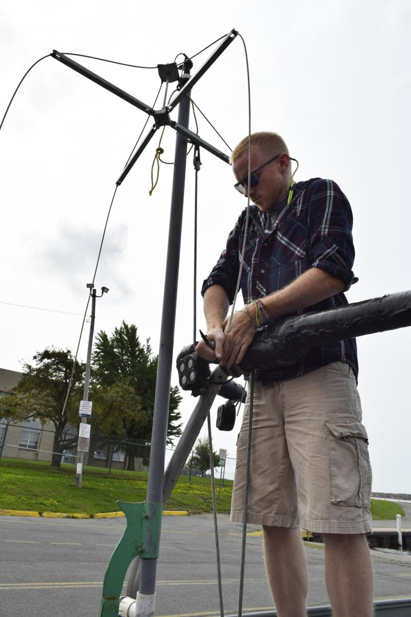 A person stands at a railing tying a rope. The rope holds a pole with wires in a vertical position.