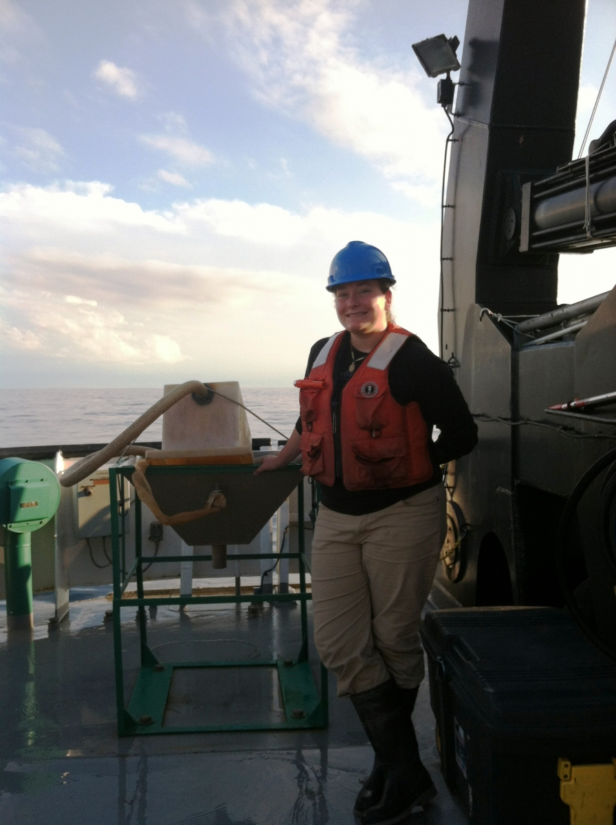 A person in a hard hat and life jacket stands on the back deck of a boat next to a metal table with something on it.