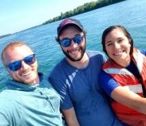 Three smiling people stand in front of the water. One is wearing a life jacket and the other two have sunglasses.