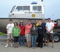 "Ten people stand in front of a boat on a trailer. The boat is named ""R/V John J. Freidhoff."""