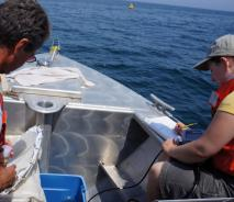 Two people working in the front of a boat. One holds a net and a bottle of reddish liquid. The other is holding a cable and instrument and writing on a datasheet