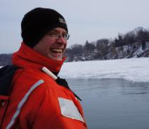 a person in a flotation coat and knit cap smiles near the icy water