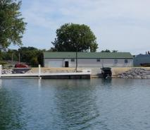 View from the water of a one-story building with a dock and ramp. The shoreline has neat stonework and there is a floating dock attached to the permanent dock structure. A truck and trailer are backed into the water after launching a boat.