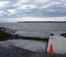 A ramp leading down the water is mostly submerged by waves. There is a line of seaweed, wood, and garbage at the waterline.