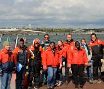 A portrait of a group of people wearing safety gear or life jackets, standing on a dock in front of a boat.