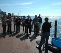 A group of people stand on a dock by the water taking notes. A person stands in front of them with some research equipment