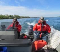Two people sit at the back of a boat while one drives. There is a net next to one of them, and both are wearing safety suits.
