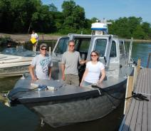 Three people stand for a picture at the front of a metal boat that's tied up to a dock.