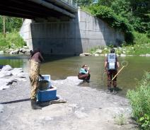 Three people stand near a creek wearing chest waders. One stands in the water with a backpack unit on and holds a pole with a wire hoop at the end. Another sits on a rock by the water. A third gets ready near a cooler with buckets in it.