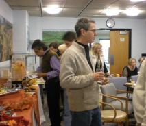 People talking, holding snacks. There is a fall-themed table with food to the left.