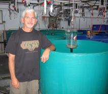 A person stands with their arm resting on a round green tank in a lab.