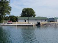 A white building with a green roof with a dock and boat launch, next to the water. A truck with a trailer is backed down the ramp toward the water.