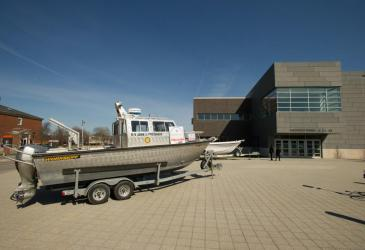 R/V John J. Freidhoff, a silver boat, sits on a trailer in front of the Burchfield Penney Art Center with a placard for the 50th anniversary of the Great Lakes Center. Part of a white boat can be seen behind the John J.