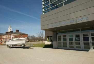 A white research boat sits on a trailer in front of the Burchfield Penney Art Center with a placard for the 50th anniversary of the Great Lakes Center.