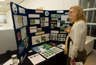 A woman stands in front of a display table for WNY PRISM.