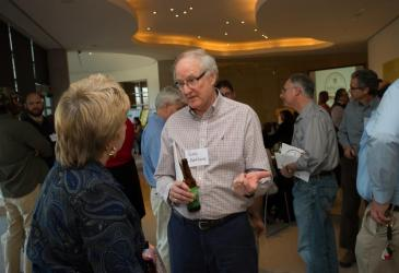 "A man whose name tag reads ""Gary Pettibone"" talks with a woman. There are many guests standing socializing behind them."
