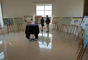 Two people stand before several easels with academic posters featuring Great Lakes work.