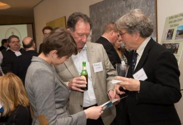 Michael Clarke, John Montague, and another guest examine the program for the anniversary reception while other guests mingle behind them.