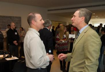 A former GLC employee, Mike Goehle, talks with Assemblyman Sean Ryan while guests mingle at the reception.