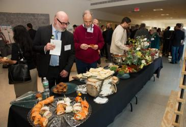 Thomas Hahn and Howard Lasker sample the hors d'oevres while guests mingle at the reception.