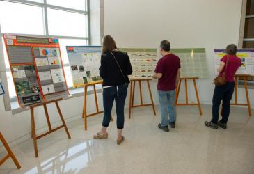Three people stand before several easels with academic posters featuring Great Lakes work.