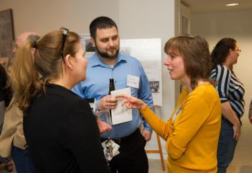 A woman facing away from the camera, Brian Hinterberger, and Dr. Alicia Pérez-Fuentetaja talk while other guests mingle at the reception.