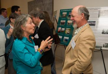 Dorothy Griffith and Roger Allen talk near GLC posters while other guests mingle at the reception.