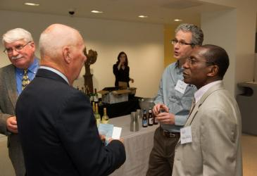 Former GLC Director Gordon Fraser (second from the left, facing away from camera) talks with field station manager Mark Clapsadl and Kofi Fynn-Aikins near the refreshment table. There are two other people in the background.