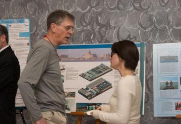 A man discusses a poster with a student presenter at the 50th anniversary reception.