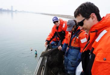 Students pulling in a trap net on a boat