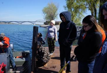 People stand on a dock next to a moored boat.