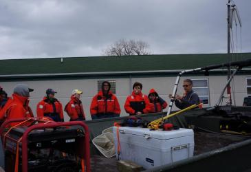 Students in orange float suits stand behind a green boat with a white cooler and a generator on it. There is a white building with a green roof behind them.