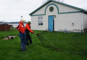 Two students in orange float suits hold a conical trap net open during an on-land demonstration. The net opens up toward the right.